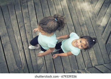Horizontal shot of two smiling small girls on wooden floor.