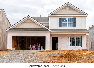 Horizontal shot of a two story House Under Construction In a New Subdivision.  All visible markings and signs have been removed.