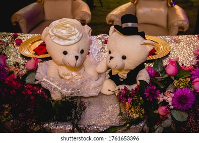 A horizontal shot of two white stuffed bears dressed as bride and groom on a decorated wedding table