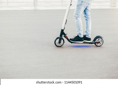 Horizontal shot of unknown male stands on electric scooter, wears sneakers and tight jeans, drives during summer time. People and transport concept