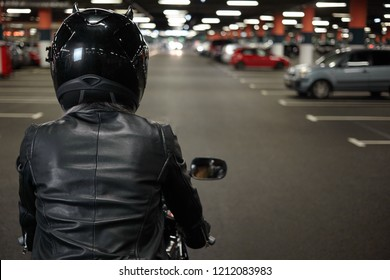 Horizontal shot of unrecognizable woman motorcycle rider driving her enduro motobike or chopper dressed in stylish leather clothes and protective equipment, blurred ligths and cars in background