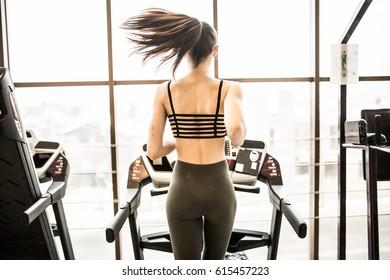Horizontal shot of woman jogging on treadmill at health club.