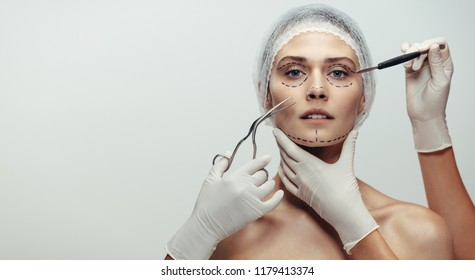 Horizontal shot of woman under going a face lift surgery. Female face with dotted line drawn and beautician holding surgical instruments on grey background.