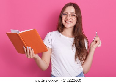 Horizontal shot of young attractive caucasian female in white casual clothes and spectacles, holding notebook and penil in hands, model posing isolated over pink studio wall. Students concept. - Shutterstock ID 1472126300
