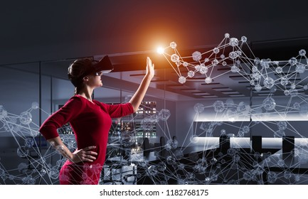 Horizontal shot of young and beautiful woman in red dress using virtual reality headset while standing indoors of dark office building with digital network structure