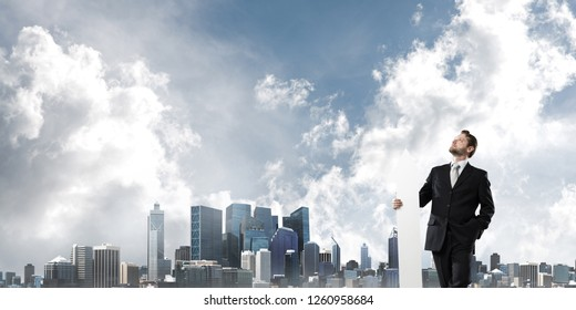 Horizontal shot of young businessman in suit keeping big white arrow in hands while standing against modern cityscape view. Modern business concept