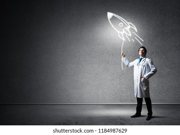 Horizontal shot of young confident doctor in white medical uniform holding glowing rocket symbol while standing against dark gray wall on background.