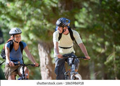 Horizontal shot of a young couple with rucksacks wearing cycling helmets mountain bike on a woodland trail smile at each other.