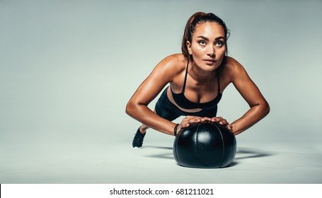 Horizontal shot of young fit woman doing push up on medicine ball. Fitness female exercising with a medicine ball on grey background.