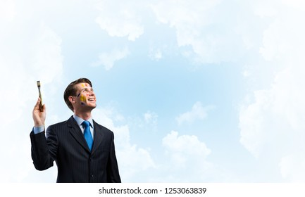 Horizontal shot of young and happy businessman in black suit holding paintbrush in his hand while standing against blue and cloudy skyscape on background.