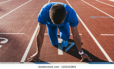 Horizontal shot of young male athlete at starting block on running track. Caucasian sprinter man in starting position for running to start a race at stadium. Sport, lifestyle and people concept.
