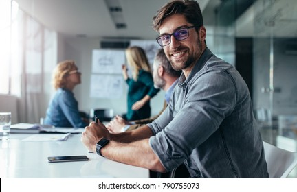Horizontal shot of young man sitting in meeting room. Businessman sitting in board room during new project discussion.