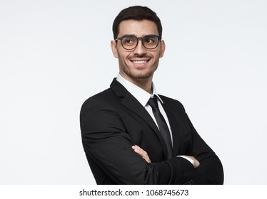 Horizontal shot of young successful smilling business man with crossed arms and side look. CEO, cheif executive officer concept.