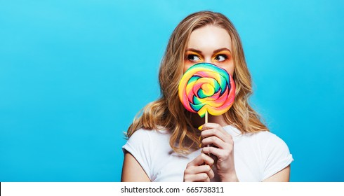 Horizontal shot of young woman holding lollipop in front of her mouth and looking away at copy space. Caucasian female model with lollipop against blue background.