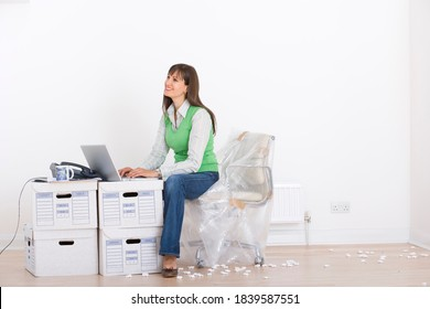 Horizontal shot of a young woman working on a laptop over a makeshift desk of boxes in an unfurnished office with copy space.