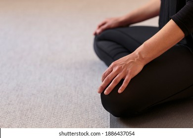 Horizontal side closeup of lower body of yogini on the floor with legs crossed in lotus pose. Woman indoors wearing black yoga pants with hands resting on knees. Peaceful meditation home yoga practice