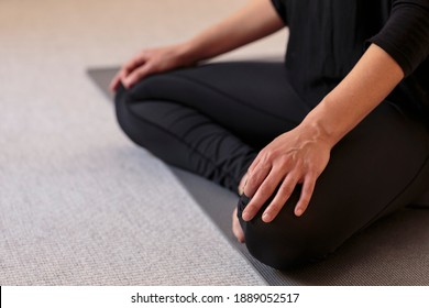 Horizontal side closeup of lower body of yogini on the floor with legs crossed in lotus pose. Woman indoors wearing black yoga pants with hands resting on knees. Home yoga practice