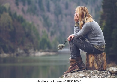 horizontal side view portrait of Caucasian young blonde woman with light colored sweater and jeans holding tree branch and meditating relaxing alone on tree stump front of lake surrounded by forest