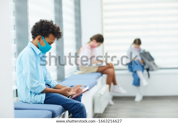 Horizontal side view shot of unrecognizable African American boy wearing mask playing mobile games while sitting in queque to school medical room, copy space
