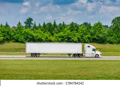 Horizontal side view shot of a white tractor-trailer with a blank trailer that would make great copy space.