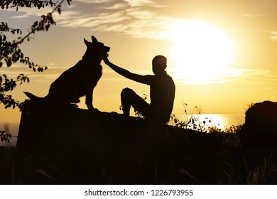 horizontal silhouette of young man and dog enjoying beautiful landscape , boy with a four-legged friend at sunset in a field, concept of harmony human and nature, happiness