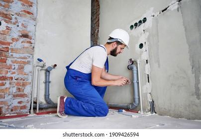 Horizontaler Schnappschuss von jungen Klempnern, die mit grauen Abwasserrohren arbeiten und diese mithilfe des Schraubenziehers an die Wand befestigen. Seitenansicht des Klempners auf Knie mit blauem Uniform- und weißem Helm