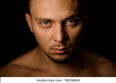 Horizontal studio portrait of the attractive muscular man with grey eyes and bristles on the black background