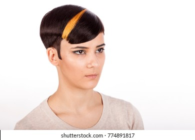 Horizontal studio portrait. Beautiful young woman with trendy highlighted short pixie haircut on white background, looking sideways.