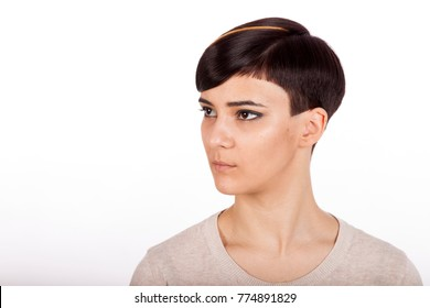 Horizontal studio portrait. Beautiful young woman with trendy highlighted short pixie hairstyle on white background, looking sideways.