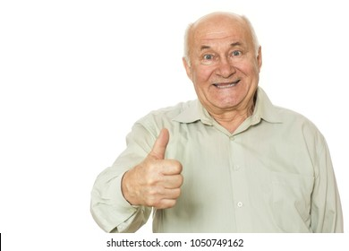 Horizontal studio portrait of a cheerful senior man smiling joyfully showing thumbs up posing isolated on white copy space. Happy grandpa having fun at studio.