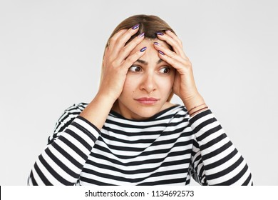 Horizontal studio portrait of desperate beautiful young woman having stressed facial expression, holding hands on her head in panic, terrified with bad negative news, doesn't know what to do