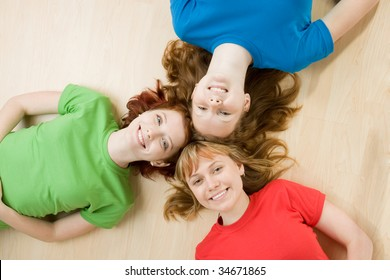 Horizontal studio portrait of three female friends lying on their backs with their heads touching in the center, isolated on a tan background.
