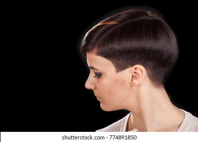Horizontal studio portrait of a young woman with androgyne look, short pixie hairstyle. Black background, sideways view