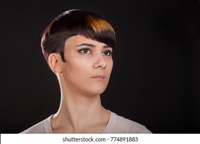 Horizontal studio portrait of a young woman with androgyne look, short pixie hairstyle. Black background