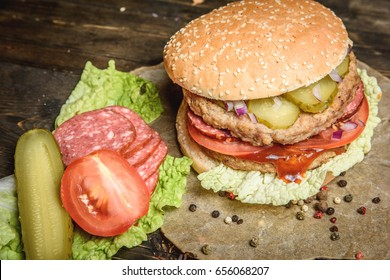 Horizontal studio shot of different vegetables and salami with tasty big hamburger on wooden board.