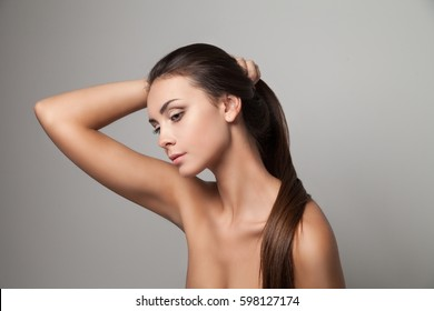Horizontal studio shot of young woman holding her long straight hair.