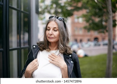 Horizontal summer image of attractive serious middle aged retired woman posing outdoors, standing at modern building dressed in stylish black leather jacket, going to get inside cafe or shop