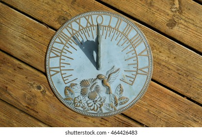 Horizontal sundial on a wooden background showing nine o'clock