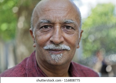 Horizontal take of a smiling asian male sporting a van dyke beard in casual western clothes  looking straight into lens. Location of shot was Istanbul, Turkey