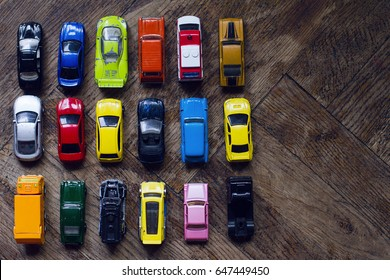 horizontal top view assorted metal colorful toy car collection on brown wooden floor in natural light copyspace