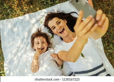 Horizontal top view of happy young beautiful mother laughing and taking self portrait with her cute kid lying on green grass and white blanket. Motherhood, technology and childhood concept.
