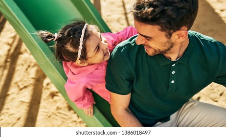 Horizontal top view image of cute happy daughter playing with her handsome father outdoors. Dad and toddler little girl having fun and playing at playground together. Father and daughter share love.