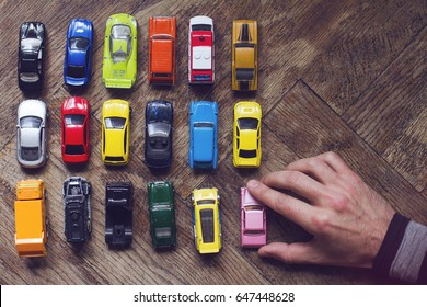 horizontal top view of male hand arranging an assorted metal colorful toy car collection on brown wooden floor in natural light