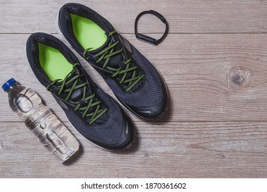 horizontal top view of a pair of black and green sport shoes, plastic bottle of water and smart wristwatch on wooden floor with copy space on the right