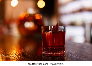 A horizontal underexposed colorful lifestyle photo of a red alcoholic drink in an old fashioned glass, on a wooden surface, lights reflecting in it, bokeh background. Selective focus.