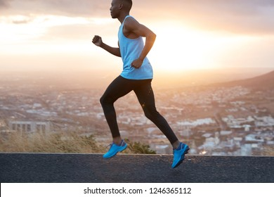 Horizontal view of active sportsman dressed in casual sportsclothes, jumps and runs on high speed, wants to come finish first and win race competition, feels strong and motivated. Sport day.
