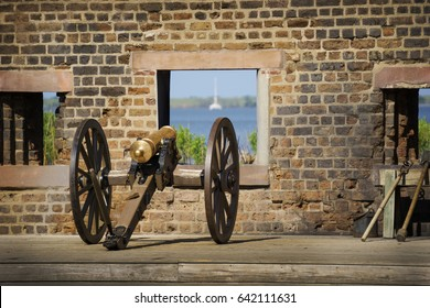 A horizontal view of an antique cannon overlooking the ocean through a window on a brown brick wall at Fort James Jackson in Savannah,Georgia.
