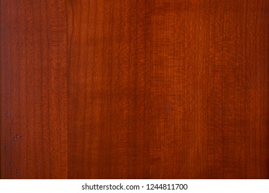 Horizontal view of a cherry wood panel with some small worm hole marks in the lower left corner.