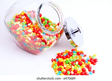 horizontal view of clear open jar and small pile of colorful jelly beans