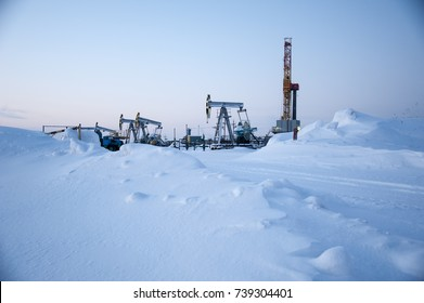 Horizontal view of a derrick drilling and pump jack in severe winter.  Extraction of oil. Petroleum concept.